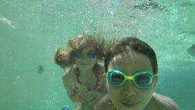 Natación de la muchacha y del muchacho debajo del agua almacen de metraje de vídeo