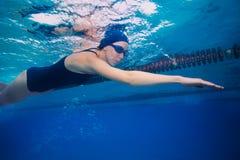 Natación de la mujer del deportista en estilo del arrastre (movimiento) fotografía de archivo