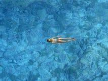 Natación de la mujer en el mar abierto Fotografía de archivo