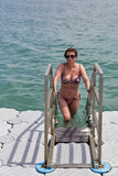 Natación de la mujer en el mar del puente de flotación imagen de archivo
