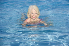 Natación de la mujer en la sonrisa al aire libre de la piscina Imagenes de archivo