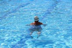 Natación de la mujer en la piscina imagenes de archivo