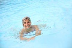 Natación de la mujer en piscina azul Imagen de archivo