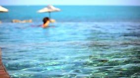 Natación de la mujer en piscina y el océano en almacen de metraje de vídeo