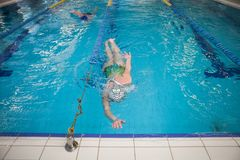 Natación de la mujer en una piscina durante la competencia fotos de archivo libres de regalías