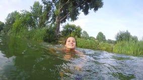Natación de la mujer joven en el lago en la cámara lenta 1920x1080 metrajes