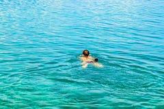 Natación de la mujer joven en el mar fotos de archivo