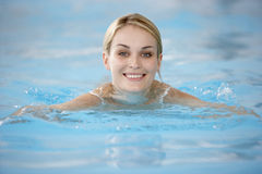 Natación de la mujer joven en piscina foto de archivo libre de regalías