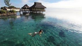 Natación de la mujer joven en una laguna coralina almacen de video