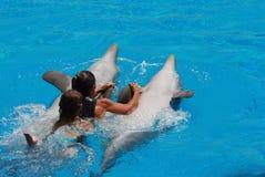 Natación de la mujer y del cabrito con los delfínes Fotos de archivo libres de regalías
