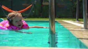 Natación de la niña en flotador en la piscina almacen de video