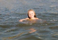 Natación de la niña en la playa imagen de archivo