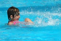 Natación de la niña en piscina de agua Fotos de archivo libres de regalías