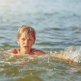 Natación de Little Boy en el río fotos de archivo