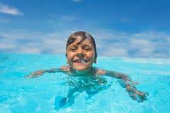 Natación de risa del muchacho en piscina al aire libre en el día soleado imagen de archivo