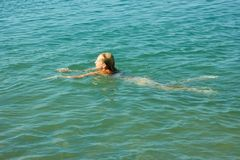 Natación del adolescente en agua de mar Fotografía de archivo