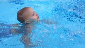 Natación del cabrito en la piscina almacen de video