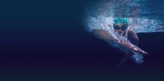 Natación del hombre en agua azul Imagenes de archivo