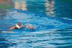 Natación del hombre en agua azul de la piscina Imágenes de archivo libres de regalías