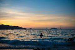 Natación del hombre en el mar después de la puesta del sol imágenes de archivo libres de regalías