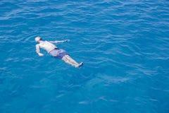Natación del hombre en el mar en el suyo detrás Fotografía de archivo libre de regalías