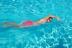 Natación del hombre joven en piscina al aire libre fotos de archivo