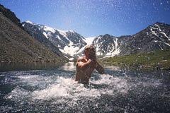Natación del hombre joven en un lago de la montaña en fondo del paisaje hermoso de la montaña con los picos coronados de nieve En imagenes de archivo