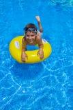 Natación del muchacho en el anillo de goma en piscina Foto de archivo