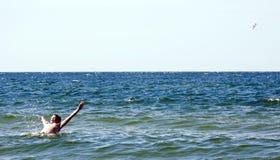 Natación del muchacho en el mar Imagen de archivo libre de regalías