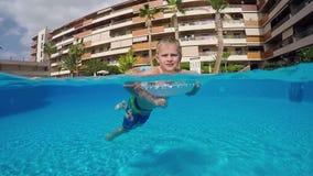 Natación del muchacho en la piscina almacen de video