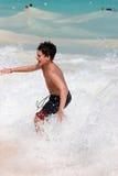 Natación del muchacho en ondas de océano Foto de archivo libre de regalías