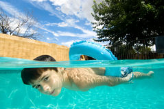 Natación del muchacho en piscina con el anillo del flotador Imagen de archivo