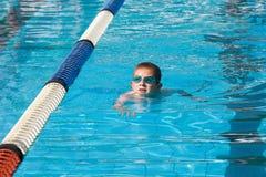 Natación del muchacho en una piscina fotografía de archivo