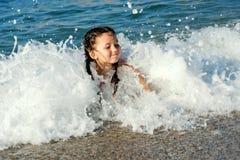 Natación del niño en el mar en ondas Imagen de archivo