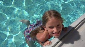 Natación del niño en la piscina, niño sonriente, retrato de la muchacha disfrutando de vacaciones de verano almacen de video