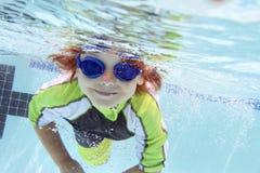 Natación del niño en la piscina subacuática imagen de archivo