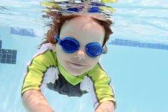 Natación del niño en la piscina subacuática Imágenes de archivo libres de regalías