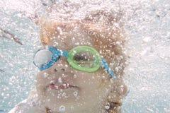 Natación del niño en la piscina subacuática Foto de archivo libre de regalías