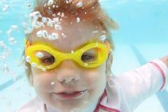 Natación del niño en la piscina subacuática Foto de archivo
