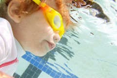 Natación del niño en la piscina subacuática Fotos de archivo