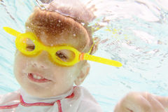 Natación del niño en la piscina subacuática Fotografía de archivo
