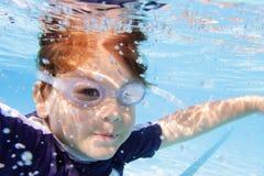 Natación del niño en la piscina subacuática Imagen de archivo libre de regalías