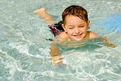 Natación del niño en piscina fotos de archivo