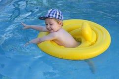 Natación del niño en piscina Imagen de archivo libre de regalías