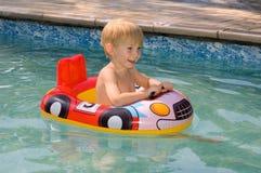 Natación del niño en una piscina Imagen de archivo libre de regalías