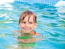 Natación del niño en una piscina Imagenes de archivo