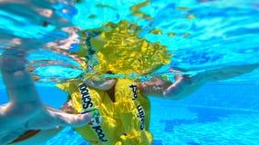 Natación del niño en una piscina, llevando un concepto inflado de las vacaciones de verano del chaleco metrajes