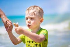 Natación del niño pequeño en el mar, el funcionamiento y salpicar en las ondas de puro fotografía de archivo