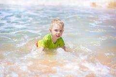 Natación del niño pequeño en el mar, el funcionamiento y salpicar en las ondas de puro fotografía de archivo libre de regalías