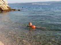 Natación del niño pequeño en el mar y la sonrisa Fotos de archivo
